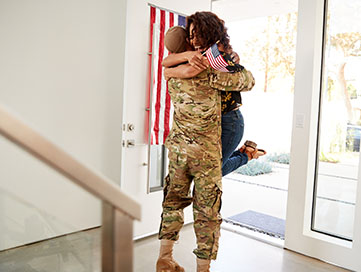 Young couple hugging as they enter their new home.
